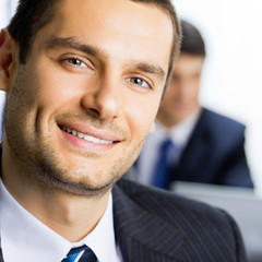 Happy smiling young businessman at office
