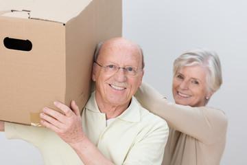 aktives älteres paar trägt umzugskarton