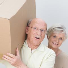 älteres paar trägt umzugskarton