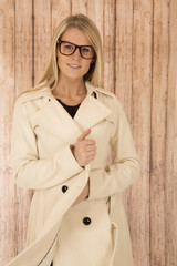 cute blonde woman wearing glasses and holding white coat closed