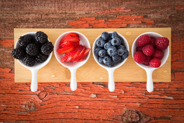 Fresh assorted berries on a grungy wooden counter