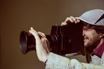 A man wearing a cap with an old movie camera.