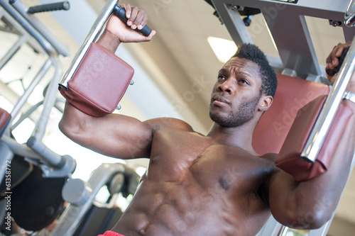 Young black man portrait exercising at the gym.