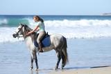 Kobieta na szarym koniu nad morzem