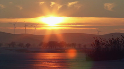 Sunset on a frozen lake with windturbines in the background