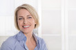 Ältere schöne blonde Frau - Portrait mit Hintergrund weiß blau