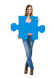 Beautiful blonde woman holding a blue piece of puzzle
