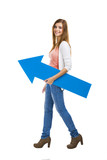 Beautiful woman walking while holding a blue arrow