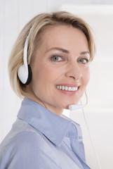 Ältere Frau lachend mit Headset arbeit im Callcenter