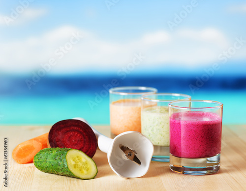 Vegetable smoothie on wooden table on the beach background