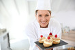canvas print picture - Smiling pastry chef showing desserts on plate