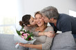 Family celebrating mother's day with bunch of flowers - 61365362