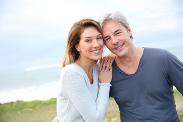 Cheerful middle-aged couple on the ocean coastline
