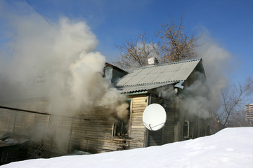 Private house in the fire puffs against a blue sky in the winter