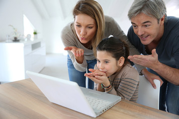 Parents with kids making a distant call on internet