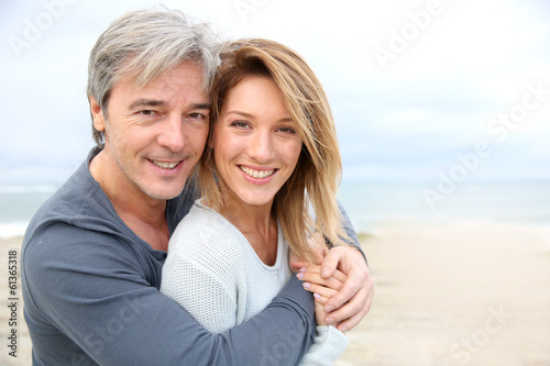 canvas print picture Cheerful mature couple embracing by the beach