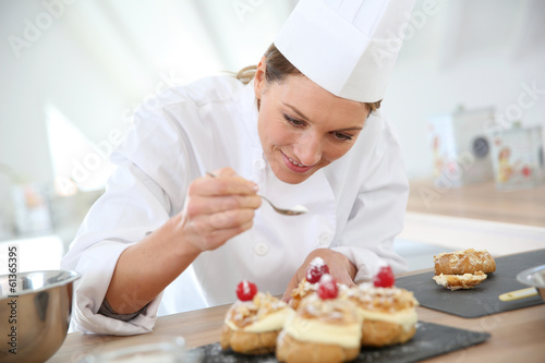 Professional cook spreading powdered sugar on cream puffs