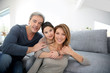 Parents with little girl relaxing on sofa