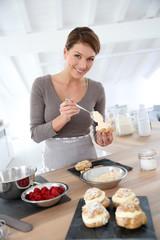 Woman in kitchen preparing cream puffs