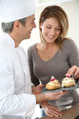 Pastry cook having woman tasting pastries