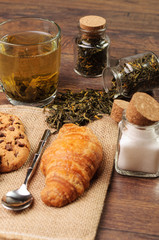 Tiny jars of tea and sugar along with a croissant