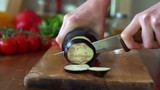 Slicing eggplant on chopping board, super slow motion,