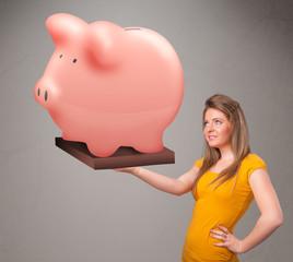 Young girl holding a huge savings piggy bank