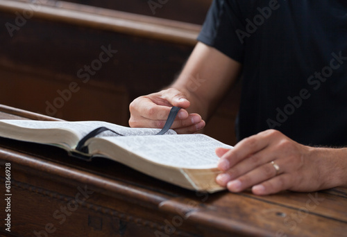 Man reading Bible in a church.