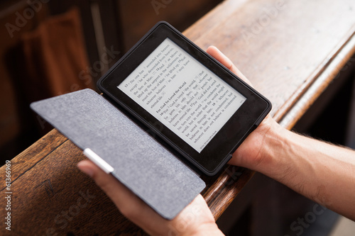 Man using tablet with Bible passage in a church.