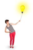 Happy woman holding a light bulb balloon