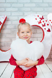 Pretty little girl holding toy heart
