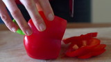 Slicing red pepper on chopping board, super slow motion,
