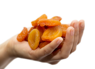 dried apricots in a hand on a white background