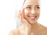 Fototapety Portrait of beautiful woman applying cream on face - isolated