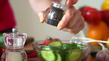 Sprinkle pepper on cucumber salad in bowl