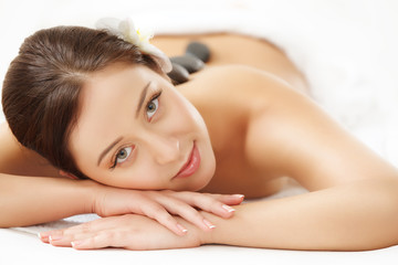 Beautiful Woman Getting Hot Stone Massage in Spa Salon.  © puhhha