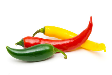 Green, yellow and red hot chili peppers on a white background