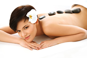 Beautiful Woman Getting Hot Stone Massage in Spa Salon.