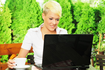 Young businesswoman on coffee break, using laptop