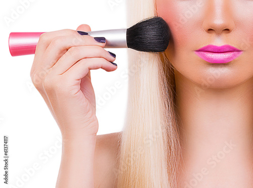 Beautiful blonde girl with makeup brush