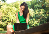 Attractive young woman with toothy smile using laptop outdoors.