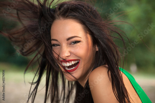 Beautiful young woman with long flying hair smiling