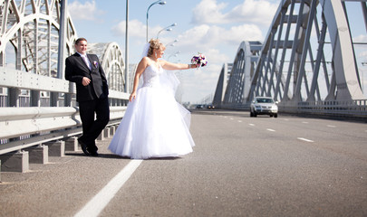 Newly married couple hitchhiking on road