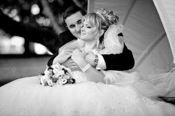 Black and white portrait newly bride lying on groom knees