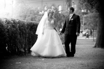 newly married couple holdings hands and walking at park