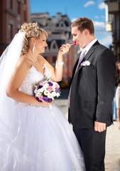 Funny  portrait of bride giving lollipop to groom
