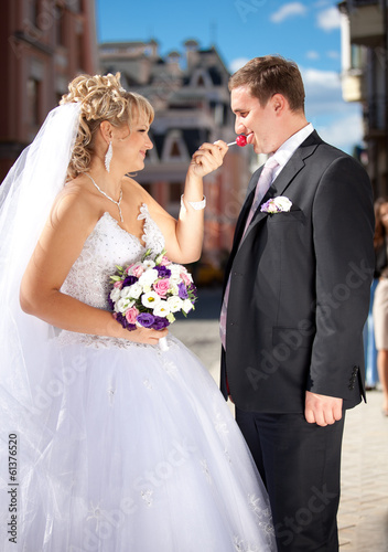 Funny  portrait of bride giving lollipop to groom