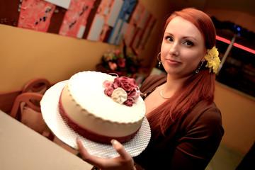 Cheerful woman holding birthday cake