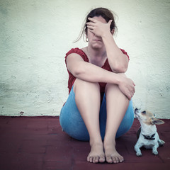 Sad woman crying with a small dog besides her