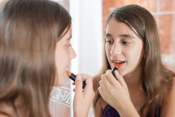 Hispanic teen putting on lipstick in front of a mirror
